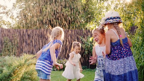 Carefree fun children play in the garden. Laughing, running under the jets of water or rain