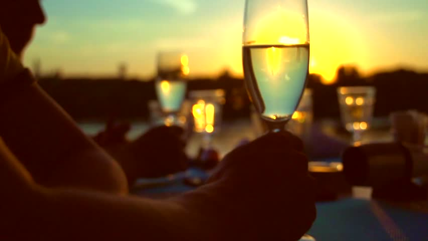 Group of people toasting and drinking champagne on the restaurant terrace over sunset. Celebrating. Glasses with Sparkling Champagne over nature Background. Resort. Slow motion full hd 1080p