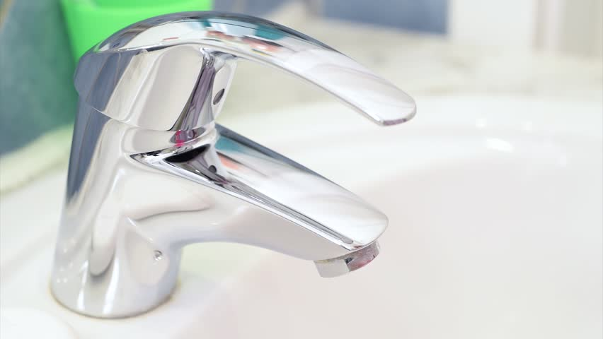 Close up of water tap in bathroom. A young woman in the morning or the evening before going to bed brushing cleaning teeth. Oral hygiene and dental health.   Shutterstock HD Video #18988033