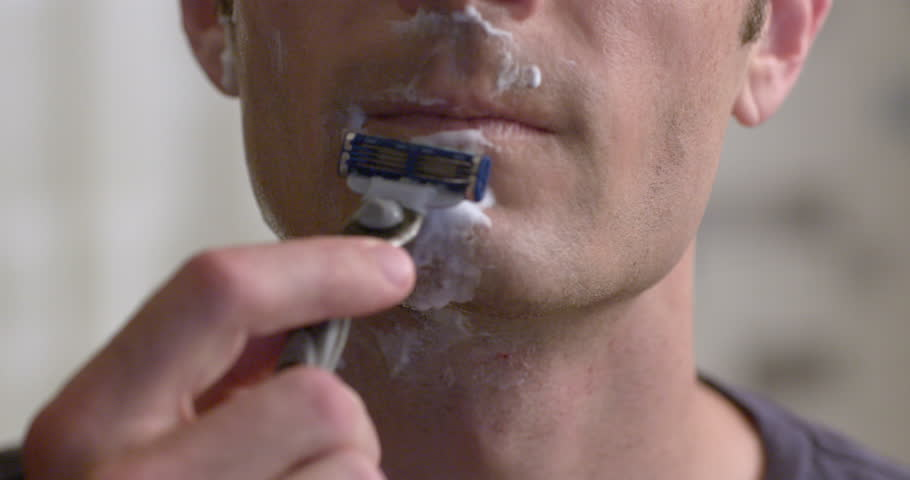 Man shaving with a wet razor and foam to remove stubble on chin.  Slow motion recorded at 60fps, extreme close up, front view.
