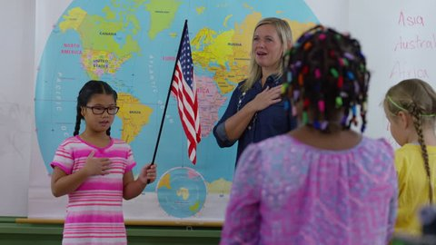 Teacher and student saying pledge of allegiance in school classroom