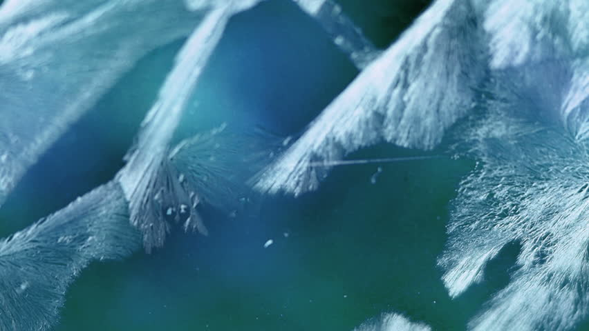 Time lapse of frost forming on a window filmed with a macro lens in HD.  Blue background, blue frost.