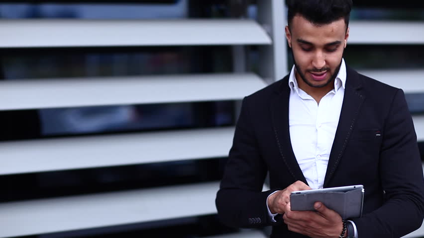 Young Handsome Businessman Arab Muslims in Business Center Wearing Dressed in Black Elegant Suit on Building Background With Tablet