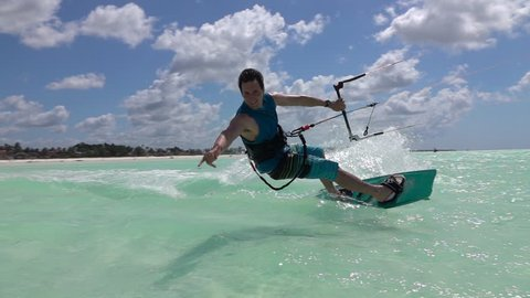 SLOW MOTION: Smiling young kiter kitesurfing and showing surf shaka sign in turquoise ocean on sunny day. Cheerful kiteboarder man kiting in beautiful tropical sandy beach lagoon on summer vacation