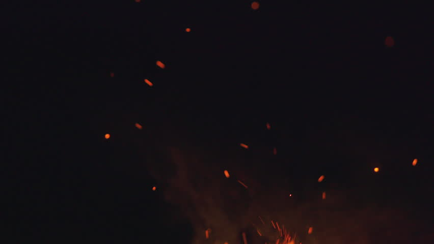 fire flames with sparks from campfire over black background