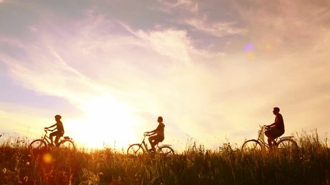 Family of three people having ride in rural landscape. Son, mother and father riding bikes over sunset sky background. Family bikers having fun on vacations.