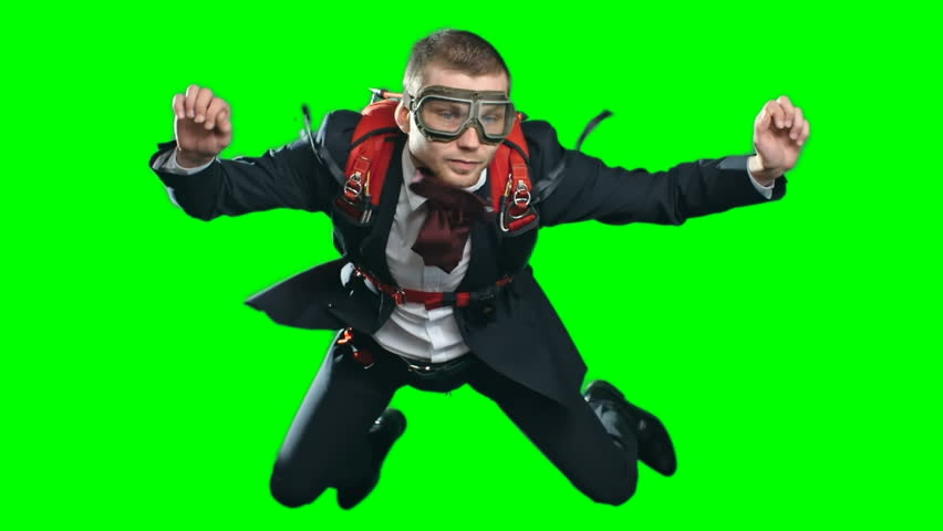 Slow motion footage of business man wearing parachute, formal suit and aviator mask, flying in mid air experiencing free fall looking calm and confident, chroma key against green screen background