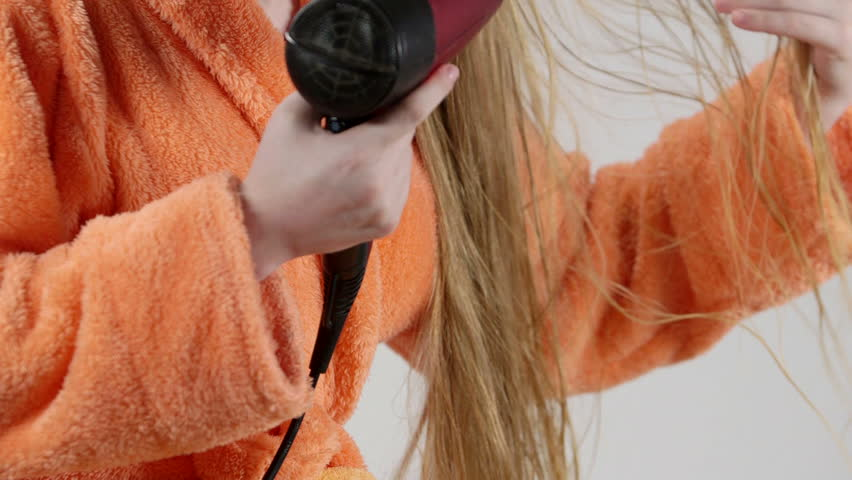 Young blonde girl in orange bathrobe blow drying her wet long hair with hairdryer
