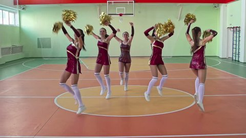 Part of cheerleader synchronized dancing performance by five elegant high school students with pom-poms wearing bright costumes in gymnasium, slow motion video