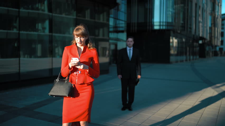 Female in red dress watch in smart phone. Male try to make offer with  digital Pad but she reject his offer. Business centre district background.  4k ultra. A a0c961d5b037