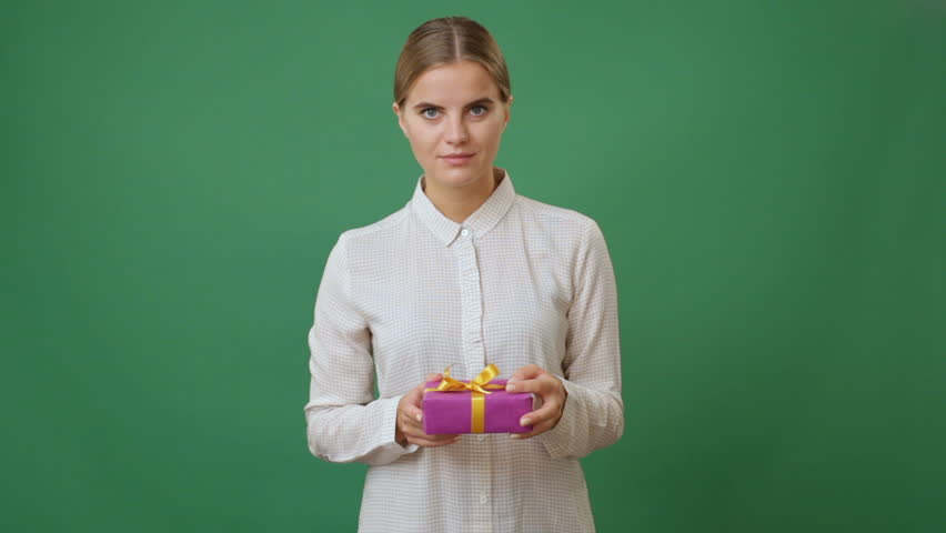 Happy young woman holding a present box and smiling against green screen   Shutterstock HD Video #19169743