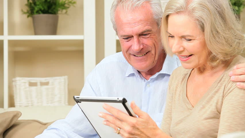 Senior couple relaxing on home sofa having fun with a modern wireless tablet