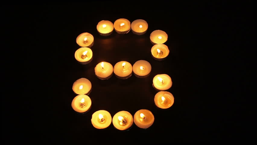 static shot of burning tealight candles arranged like pixel art numeral digits to represent the number - Halloween Background Video