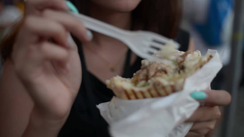KRAKOW, POLAND - JULY 27, 2016: Woman eating Doner Kebab at the night street Krakow - close up