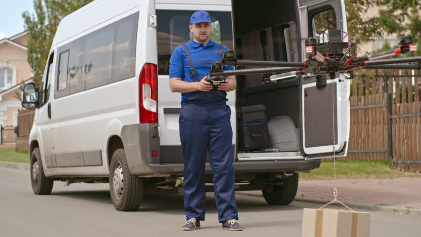 Deliveryman using remote control to operate drone transporting package to customer | Shutterstock HD Video #19225243