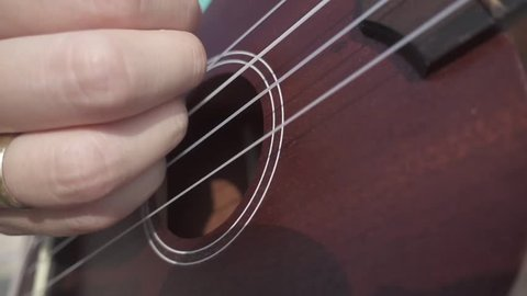 Woman's Hand Plays Ukulele. Close Deck View. Slow Motion