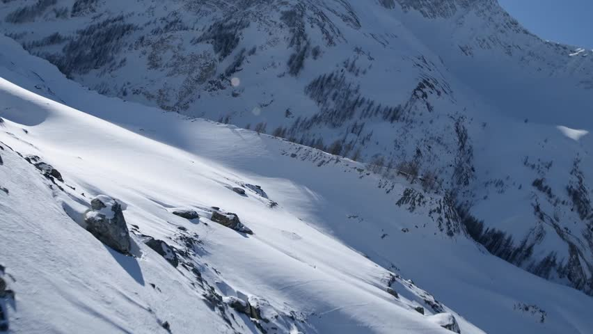 Slow Mo Aerial close shot of a snowy valley in the sun in Courmayeur, Aosta Valley/Italy (Courmayeur, Aosta Valley/Italy - March, 2016)