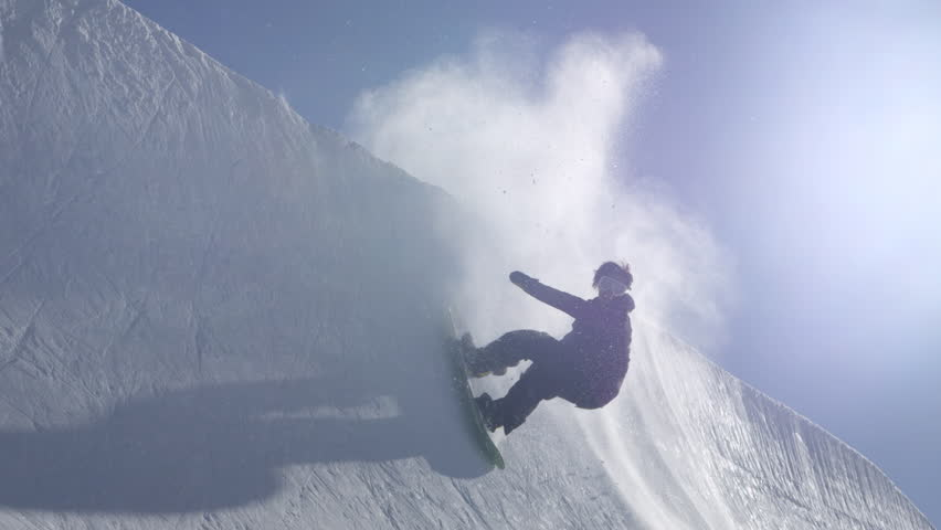 SLOW MOTION: Young pro snowboarder riding the half pipe in big mountain snow park, performing spraying trick on halfpipe wall lip in sunny winter