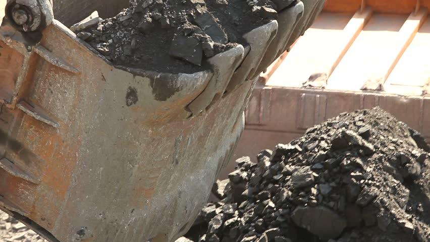 Excavator on the iron ore opencast, Loading of iron ore on very big dump-body truck, Dump truck being loaded with iron ore on the opencast, excavator bucket, close-up