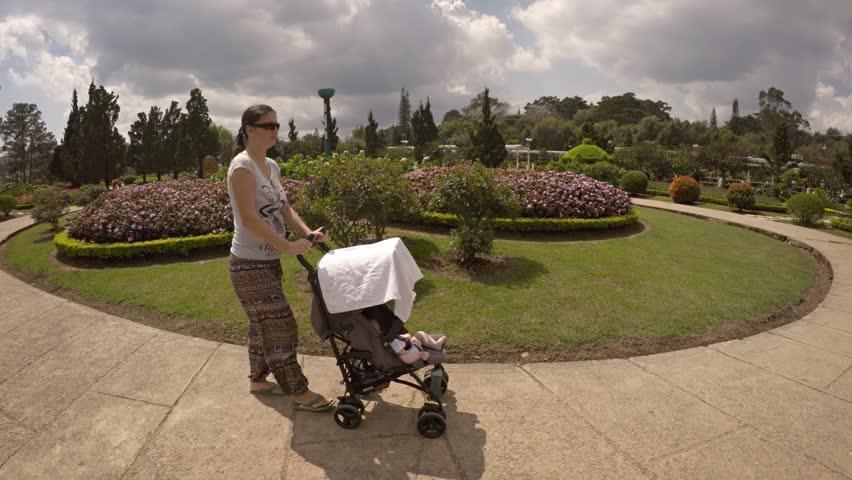 DALAT. VIETNAM - CIRCA JAN 2016: Mother pushes a baby stroller around Flower Garden Park in Dalat. Vietnam. Video 4k