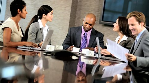 Team of five multi ethnic business people in city clothes meeting in a modern office boardroom