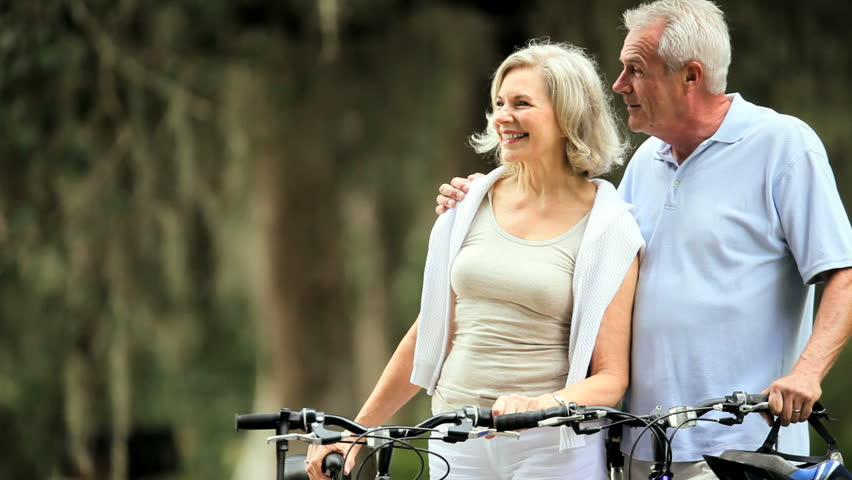 Active senior couple enjoying their retirement lifestyle out cycling