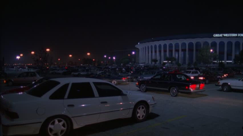 night pan right across full parking lot cars leaving coming along Great Western Forum LA forum, indoor arena House Lakers basketball team from 1967 1999 , concert venue font color red Needs additional