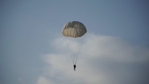 paratrooper landed on the grass and blue sky with clouds, white parachute