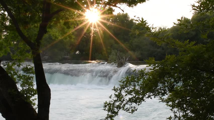 Manavgat waterfall in Turkey. Trees with green leaves in front of waterfall and sunset. | Shutterstock HD Video #19272613