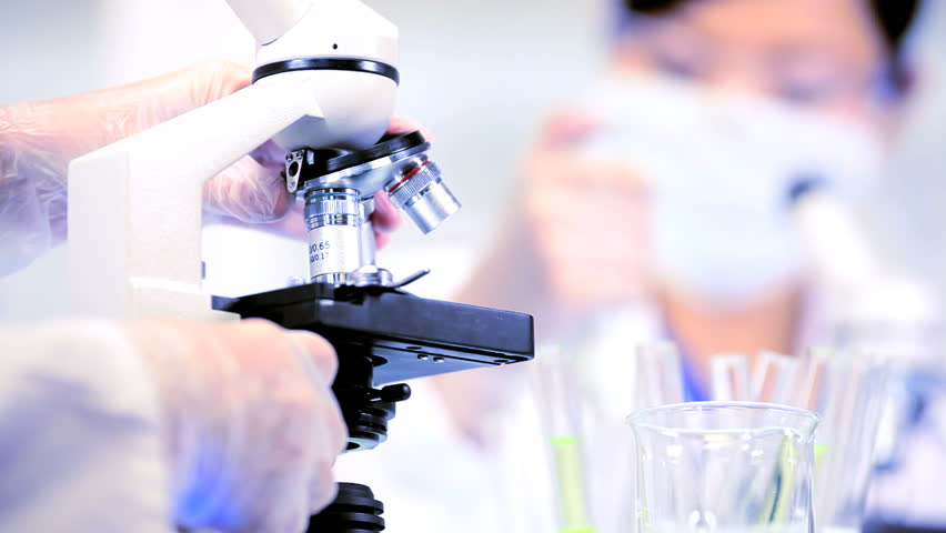 Laboratory researchers working with science equipment in sterile conditions