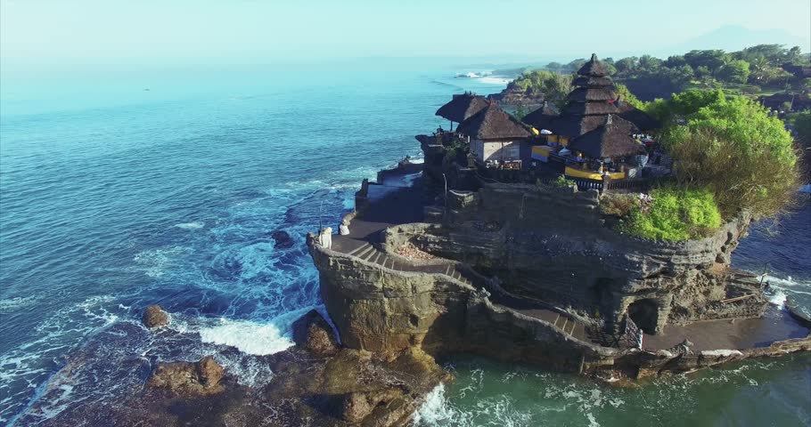 Breathtaking aerial view of of Tanah Lot Temple. Tanah Lot is a rock formation off the Indonesian island of Bali. It's home to the pilgrimage temple Pura Tanah Lot, a popular tourist and cultural icon
