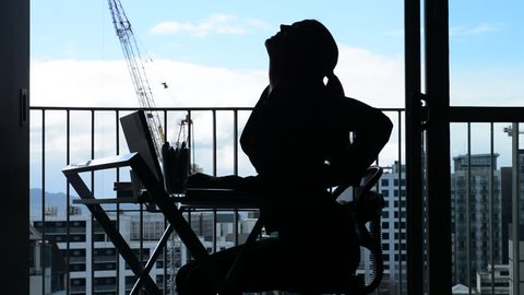 Side view Silhouette of Young woman (age 30-40) having back pain while working at desk in office. Woman work healthcare lifestyle concept. Real people. copy space