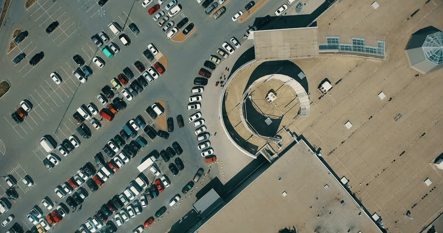 Aerial overlooking the parking with cars and people. Shoot from drone. 4K video