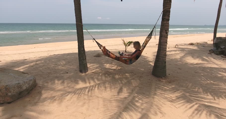 Young female successful freelancer is talking on mobile phone, while  relaxing in hammock with portable - Man Asleep On A Hammock That Floats Over The Caribbean Sea In