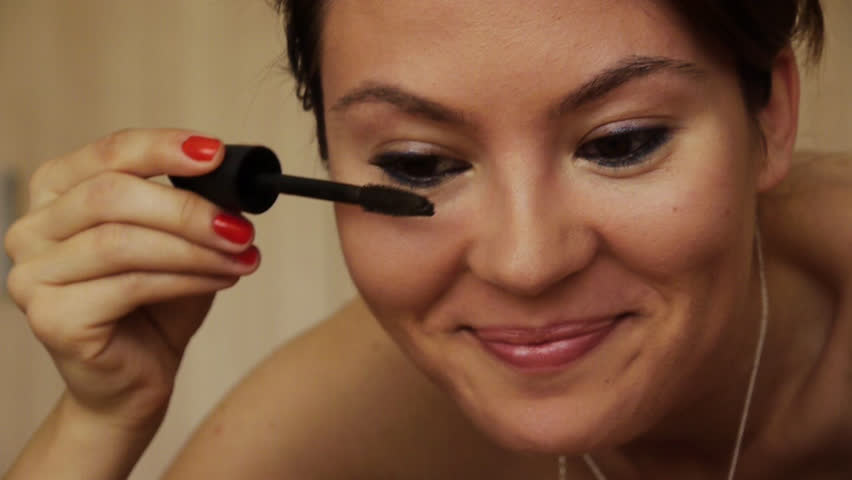 Beautiful Girl smiling brightly when making up. Using mascara with her eye lashes.