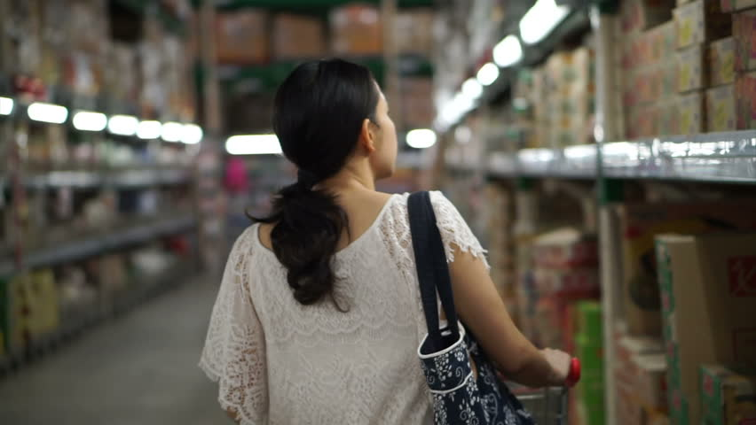 Chiangmai, Thailand - September 2016: Asian girl, woman walking, looking and shopping in supermarket isle