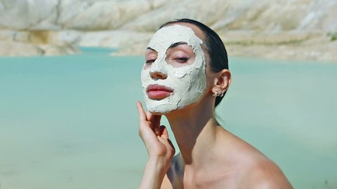 Woman with Blue Clay Facial Mask. Beauty, Wellness. Spa Outdoor, Beautiful Young Woman with natural Dead Sea mud Facial Mask on her Face near the Lake with Blue and White Cosmetic Healing Clay