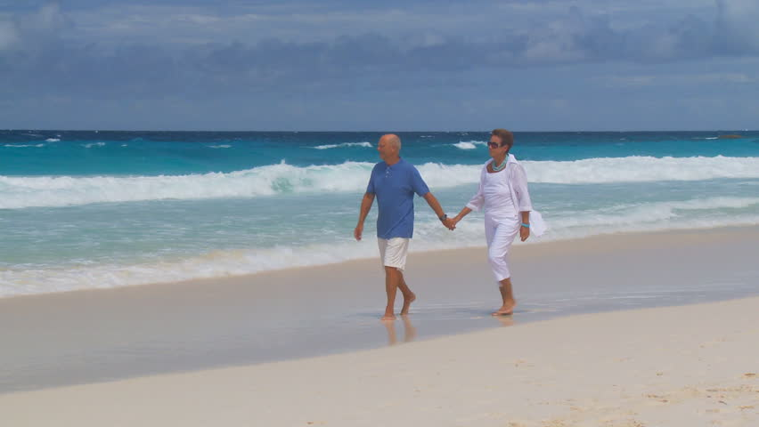 camera following senior couple walking on the beach