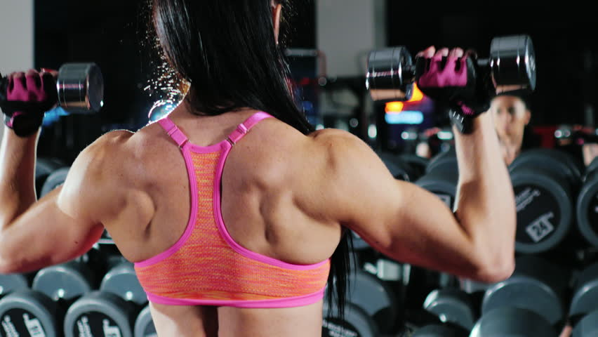Self-confident athletic woman is engaged in a sports hall. Trains with a dumbbell   Shutterstock HD Video #19363393