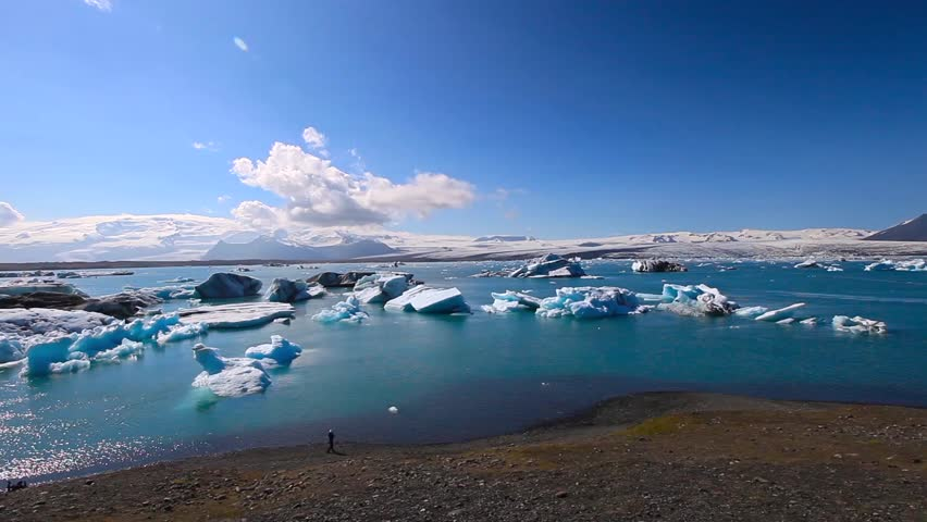 Blue icebergs floating in the sun on the glacier lake Joekulsarlon in Iceland | Shutterstock HD Video #19368433