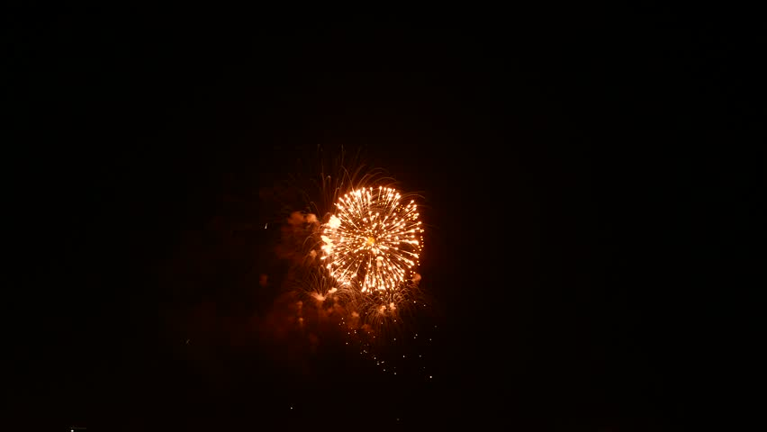 Orange and green salute explosions isolated in black sky, set of firework flashes during annual celebration of World War two victory. Round clouds of particles appear and fade in dark skies