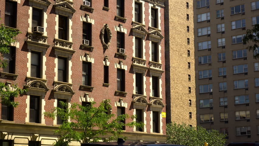 Exterior DX establishing shot outside looking up to a brick apartment building in New York City on a bright summer day