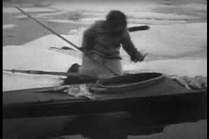 An Eskimo packs up his fishing gear and gives a fellow fisherman a ride back to shore in his kayak in 1922. (1920s)
