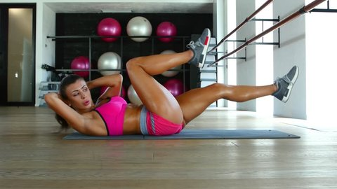 Sportive woman doing abs exercises to have flat belly, training in fitness club. Dolly shot
