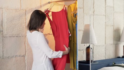 Angry woman trying to choose dress from wardrobe in room at home
