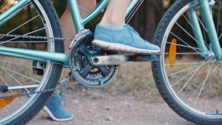 Young beautiful female riding bike - detailed pedals and wheels