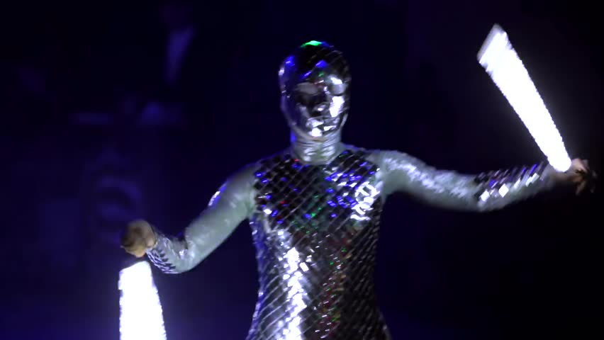 """MOSCOW, RUSSIA - JANUARY 30, 2016: Final of Moscow stage of National Cup of """"Robot wars-2016"""" at VDNH. Close view of woman performing on arena in darkness in strange alien costume and with lightsabers"""