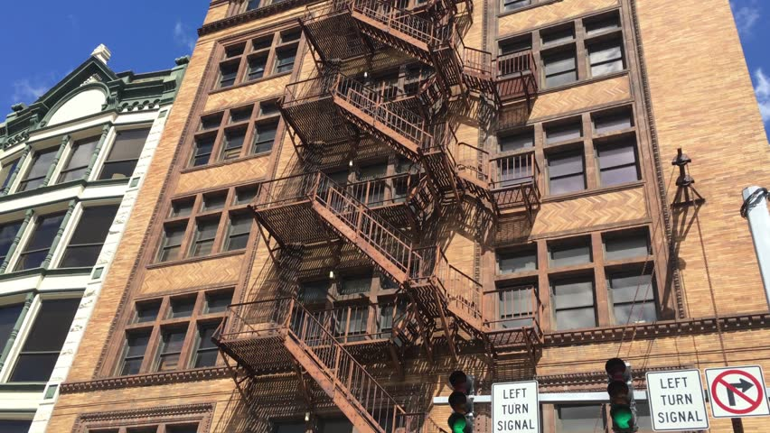 A Daytime Elishing Shot Of An Apartment Or Office Building With Fire Escape On The Front