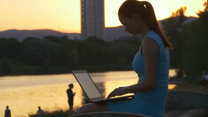 Young woman is typing on a laptop and smiling to beautiful light of the setting sun | Shutterstock HD Video #19480903