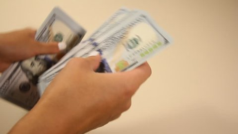 woman recounts a wad of money out of hundred dollar bills
